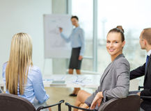 Businesswoman with team showing in office Stock Image
