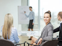 Businesswoman with team showing in office Stock Images