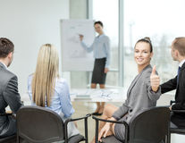 Businesswoman with team showing thumbs up Stock Images