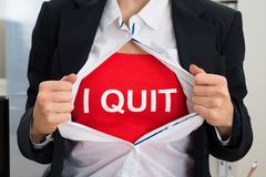 Businesswoman Tearing Off Shirt With I Quit Sign. Midsection of businesswoman tearing off shirt with I Quit sign stock photos