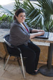 Businesswoman - Telecommuting from Internet Cafe. Stock photo of a well dressed businesswoman looking up at the camera and smiling as she works on a laptop while stock photo