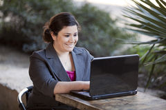 Businesswoman - Telecommuting from Internet Cafe. Stock photo of a well dressed businesswoman looking down at a laptop while telecommuting from an internet cafe royalty free stock images