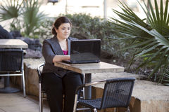Businesswoman - Telecommuting from Internet Cafe. Stock photo of a well dressed businesswoman looking down at a laptop while telecommuting from an internet cafe stock photos