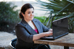 Businesswoman - Telecommuting from Internet Cafe. Stock photo of a well dressed businesswoman looking up at the camera and smiling as she works on a laptop while royalty free stock photos