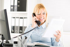 Businesswoman telephoning. Beautiful Businesswoman telephoning and working in the office Stock Images