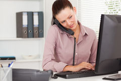 Businesswoman telephoning and typing. A businesswoman is telephoning and typing Stock Images