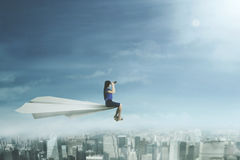 Businesswoman with telescope on paper plane Royalty Free Stock Photo