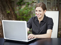 Businesswoman teleworking at home. On a Laptop. Smiling Royalty Free Stock Photography