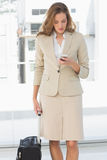 Businesswoman text messaging while on a business trip. Beautiful young businesswoman text messaging while on a business trip Royalty Free Stock Photo