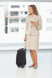 Businesswoman text messaging while on business trip. Full length of a beautiful young businesswoman text messaging while on a business trip Royalty Free Stock Photography