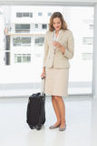 Businesswoman text messaging while on a business trip. Full length of a beautiful young businesswoman text messaging while on a business trip Royalty Free Stock Photos