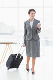 Businesswoman text messaging while on a business trip. Full length of a beautiful young businesswoman text messaging while on a business trip Stock Images