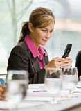 Businesswoman text messaging on cell phone. In conference room Stock Image
