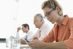 Businesswoman Text Messaging On Cell Phone At Conference Table Royalty Free Stock Photos
