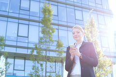 Businesswoman text messaging through cell phone on sunny day Royalty Free Stock Image