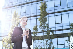 Businesswoman text messaging through cell phone on sunny day Stock Photos