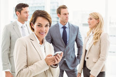 Businesswoman text messaging with colleagues in meeting behind Stock Photo