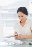 Businesswoman text messaging in front of computer at desk Royalty Free Stock Photography