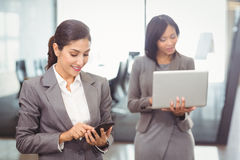 Businesswoman text messaging on mobile phone Royalty Free Stock Images
