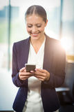 Businesswoman text messaging on mobile phone Stock Image