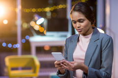 Businesswoman text messaging on mobile phone Stock Photos