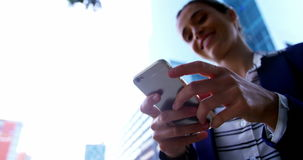 Businesswoman text messaging on mobile phone. While standing at city street stock video footage