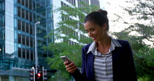 Businesswoman text messaging on mobile phone. While walking at city street stock video footage