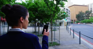 Businesswoman text messaging on mobile phone. While walking at city street stock footage