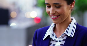 Businesswoman text messaging on mobile phone. While walking at city street stock video