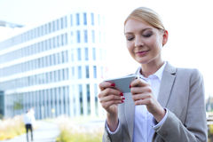 Businesswoman text messaging through smart phone outdoors Royalty Free Stock Photos