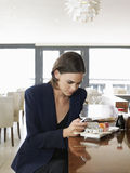 Businesswoman Text Messaging In Sushi Restaurant Stock Photo