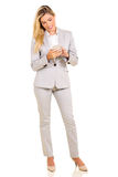 Businesswoman texting. Happy businesswoman texting on her cell phone Royalty Free Stock Photos
