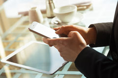 Businesswoman texting with her mobile during a coffee break Royalty Free Stock Photography