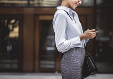 Businesswoman texting on her phone Stock Photo