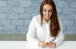 Businesswoman texting on her smartphone Stock Image