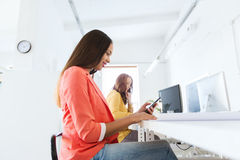 Businesswoman texting on smartphone at office Stock Photos