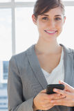 Businesswoman texting and smiling at camera Royalty Free Stock Photography