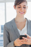 Businesswoman texting and smiling Stock Photo