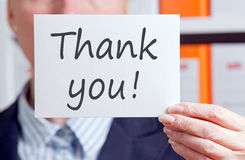 Businesswoman with a thank you sign. Closeup of a businesswoman holding a thank you sign in an office Stock Photos