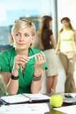 Businesswoman thinking. Portrait of young businesswoman sitting at office desk, thinking Royalty Free Stock Photography