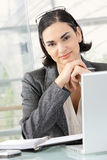 Businesswoman thinking. Young businesswoman thinking leaning on hands, sitting at office desk Stock Images
