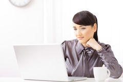 Businesswoman thinking. Young businesswoman thinking over her laptop Stock Image