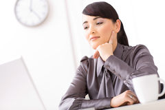 Businesswoman thinking. Young businesswoman thinking in her office leaning on her hand Royalty Free Stock Photo