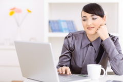 Businesswoman thinking. Portrait of attractive young businesswoman thinking over her laptop computer, leaning on her hand Royalty Free Stock Images