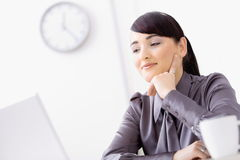 Businesswoman thinking. Young businesswoman thinking over her laptop, leaning on her hand, smiling Stock Photo