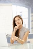 Businesswoman thinking at desk. Using laptop computer, concentrating, looking up Royalty Free Stock Images