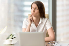 Businesswoman thinking about difficult question. Woman with pensive facial expression looking aside while sitting at workplace. Unsure businesswoman thinking Stock Image