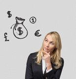 Businesswoman thinking. And drawing money bag on wall Royalty Free Stock Images