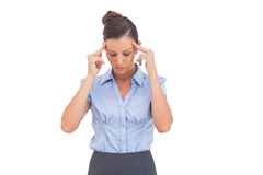 Businesswoman thinking with fingers on her temples Royalty Free Stock Image