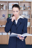 Businesswoman thinking. Businesswoman reading product catalog and thinking in office Stock Image